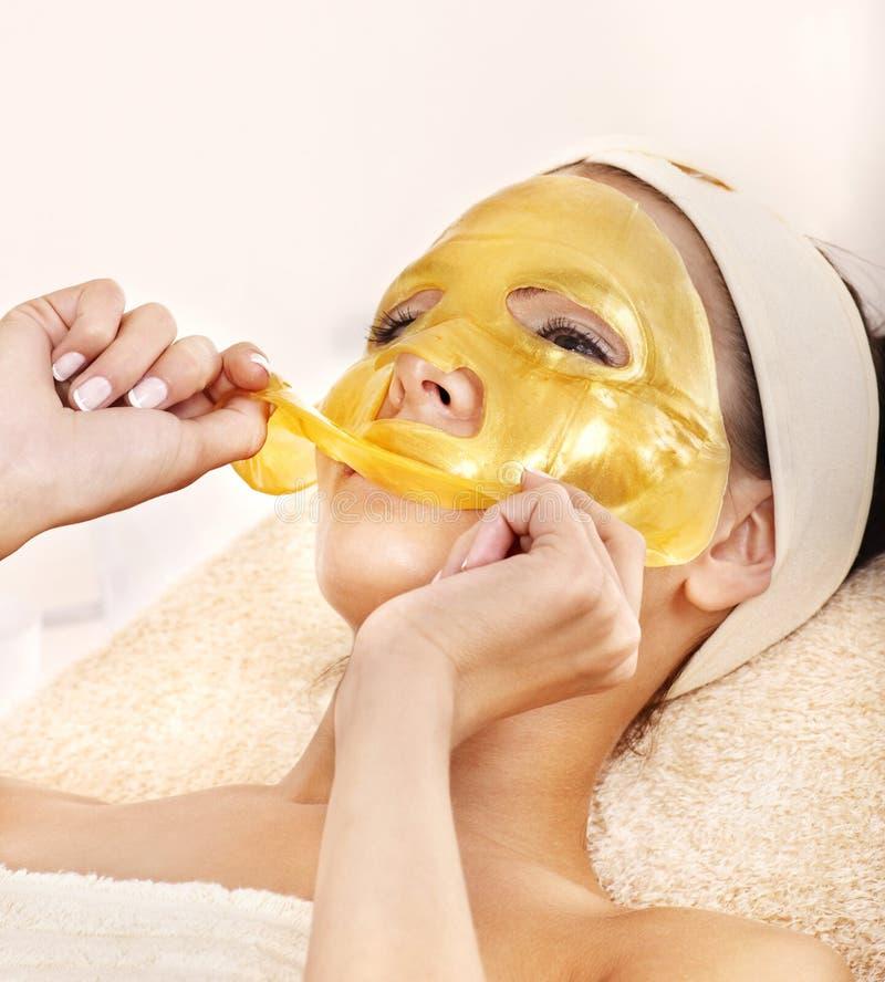 Muchacha con la máscara del facial del oro. imagen de archivo