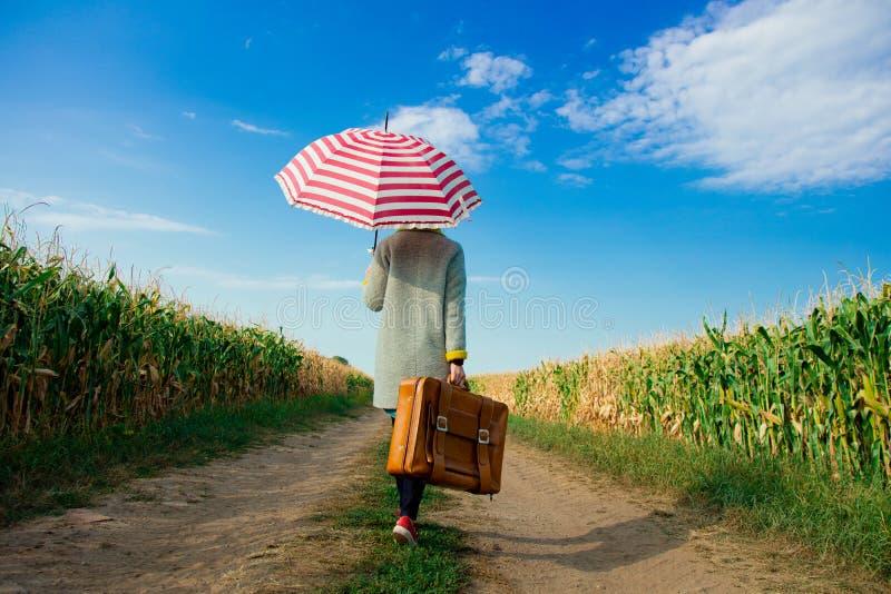 Muchacha con la maleta y el paraguas cerca del campo de maíz fotos de archivo libres de regalías