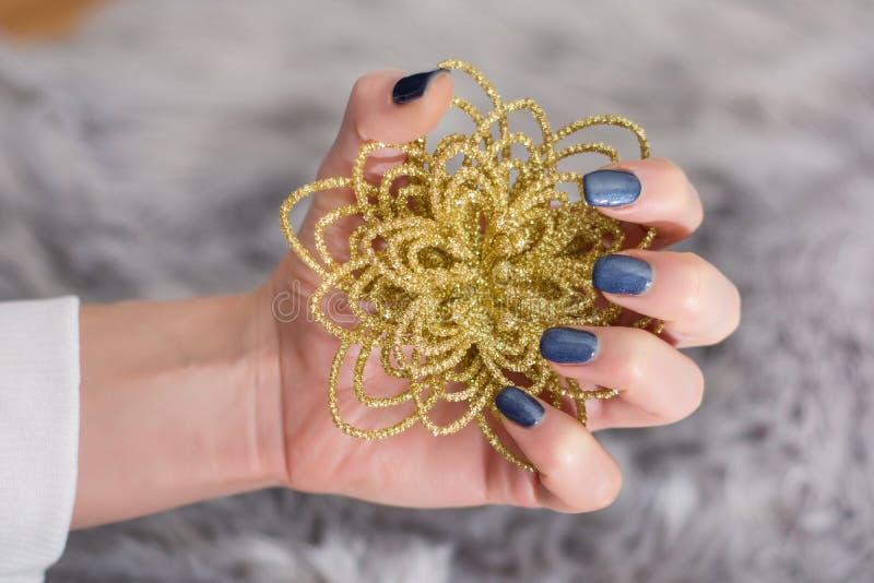 Muchacha con la manicura de los azules marinos en los clavos del finger que sostienen la flor de oro decorativa imagen de archivo