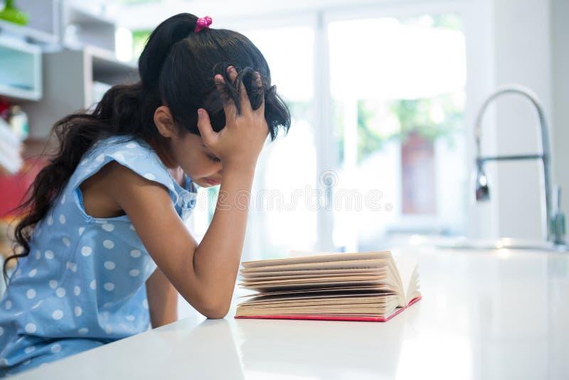 Muchacha con la mano en novela de la lectura del pelo en cocina fotografía de archivo libre de regalías