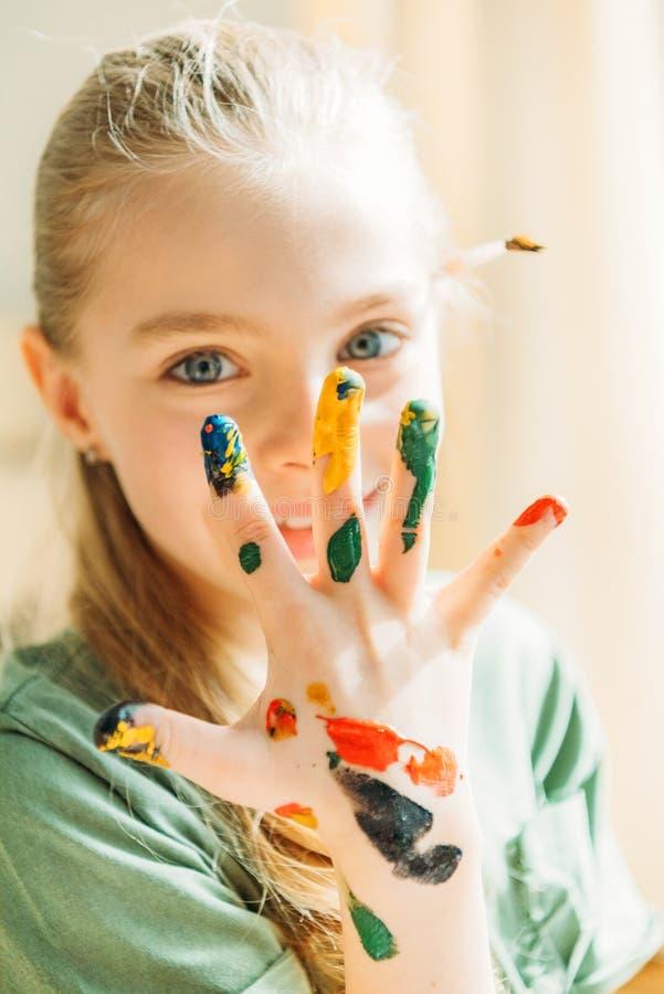 Muchacha con la mano pintada que mira la cámara niños que dibujan concepto de la escuela imagenes de archivo