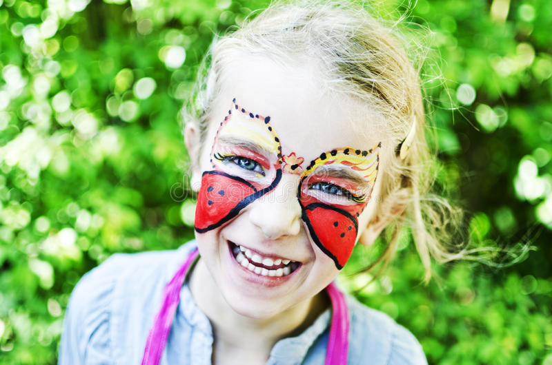 Muchacha con la mariposa pintada de la cara imagen de archivo libre de regalías