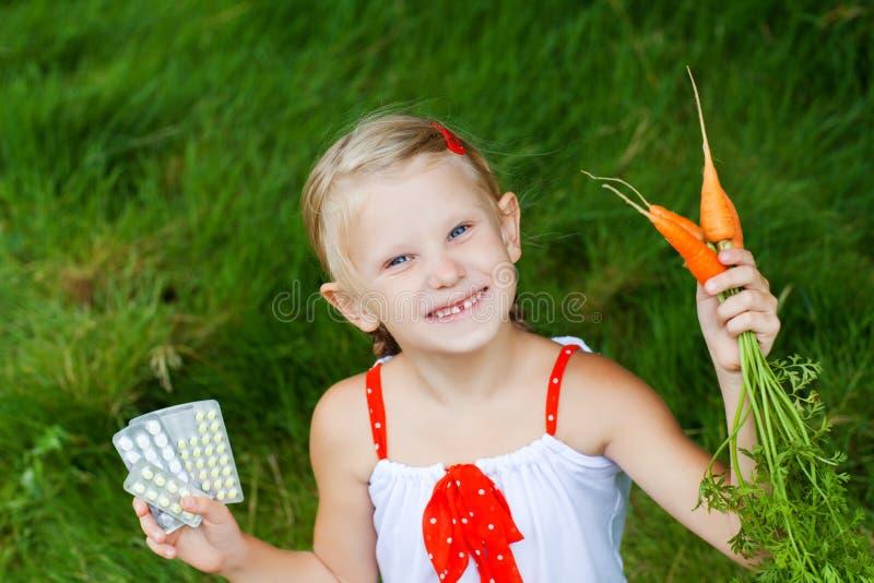 Muchacha con la medicina y las zanahorias foto de archivo libre de regalías