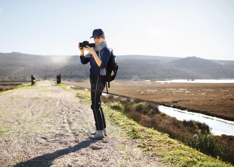 Muchacha con la mochila y cámara que despiertan en las rocas fotos de archivo