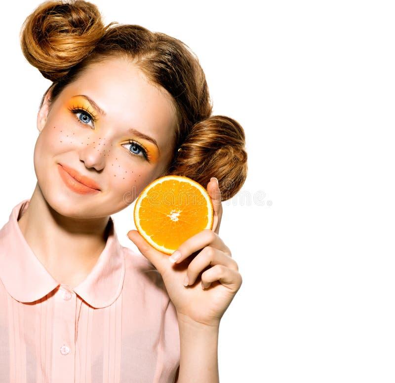 Muchacha con la naranja jugosa fotos de archivo