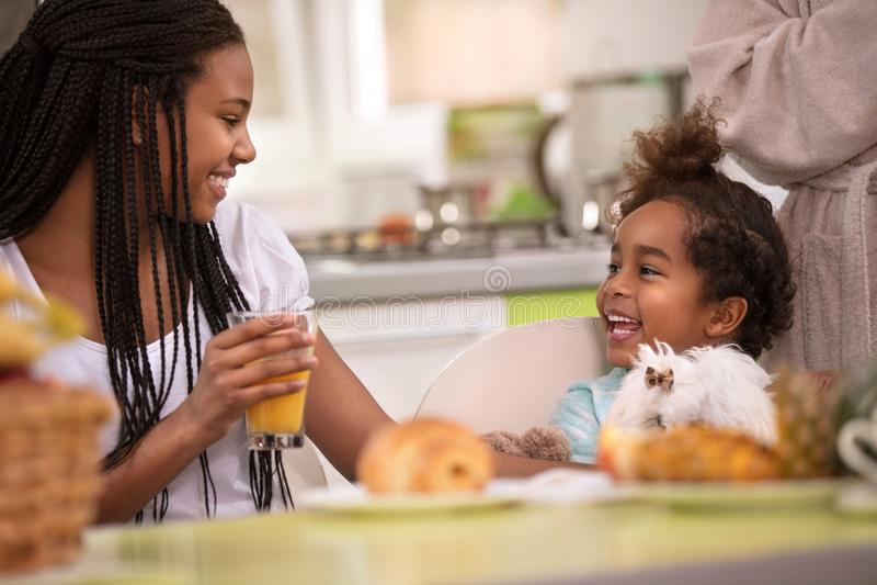 Muchacha con la pequeña hermana en la tabla que desayuna imagen de archivo