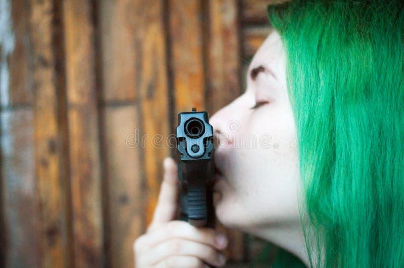 Muchacha con la pistola y el pelo verde fotografía de archivo
