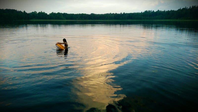 Muchacha con la rueda de agua en el lago en la tarde imagenes de archivo