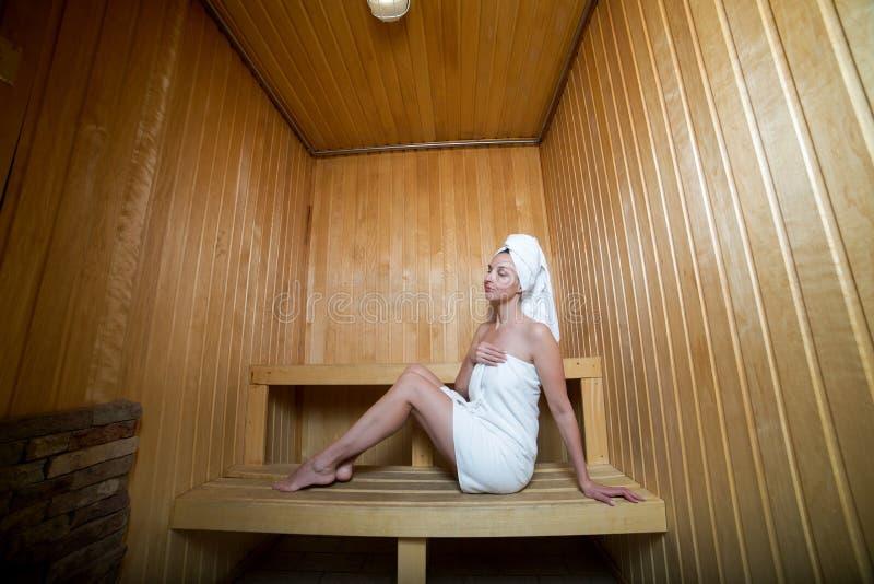 Muchacha con la sentada blanca del traje fotografía de archivo libre de regalías