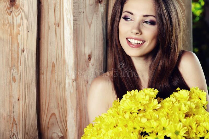 Muchacha con la sonrisa amarilla de las flores foto de archivo