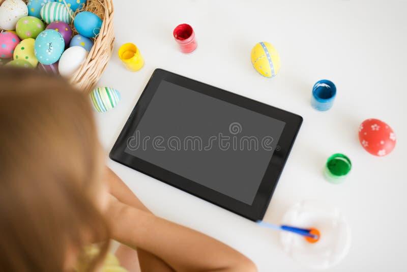 Muchacha con la tableta, los huevos de Pascua y los colores fotos de archivo libres de regalías