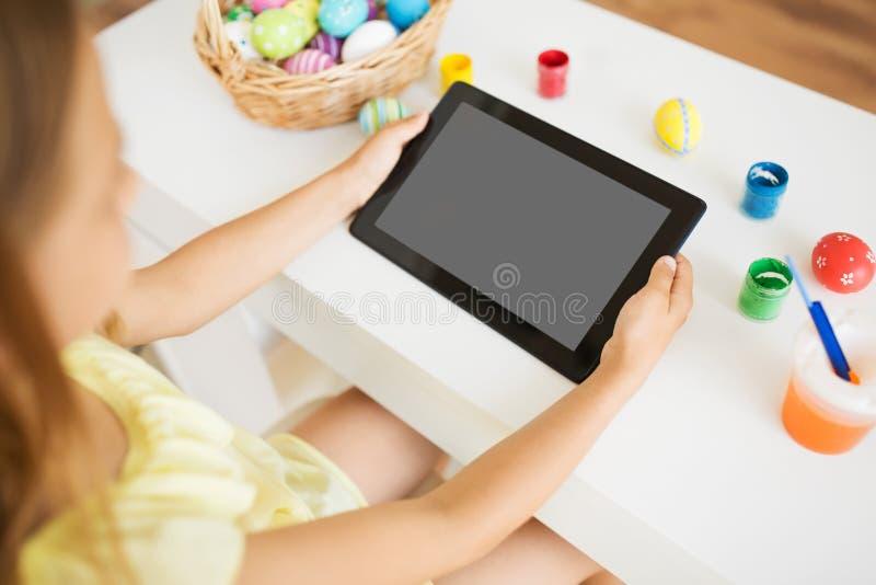Muchacha con la tableta, los huevos de Pascua y los colores imagen de archivo libre de regalías