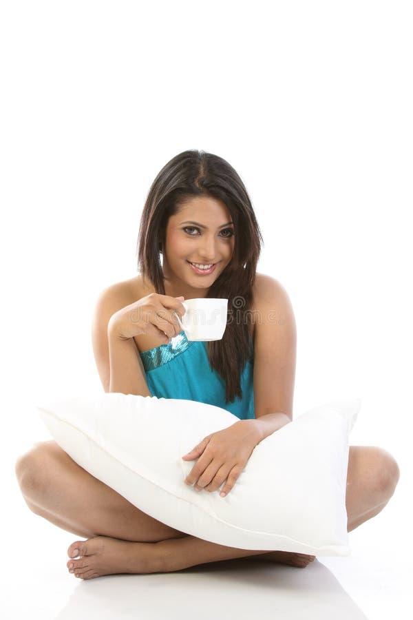Muchacha con la taza de café de la explotación agrícola de la almohadilla imagen de archivo