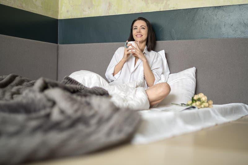 Muchacha con la taza en cama foto de archivo libre de regalías