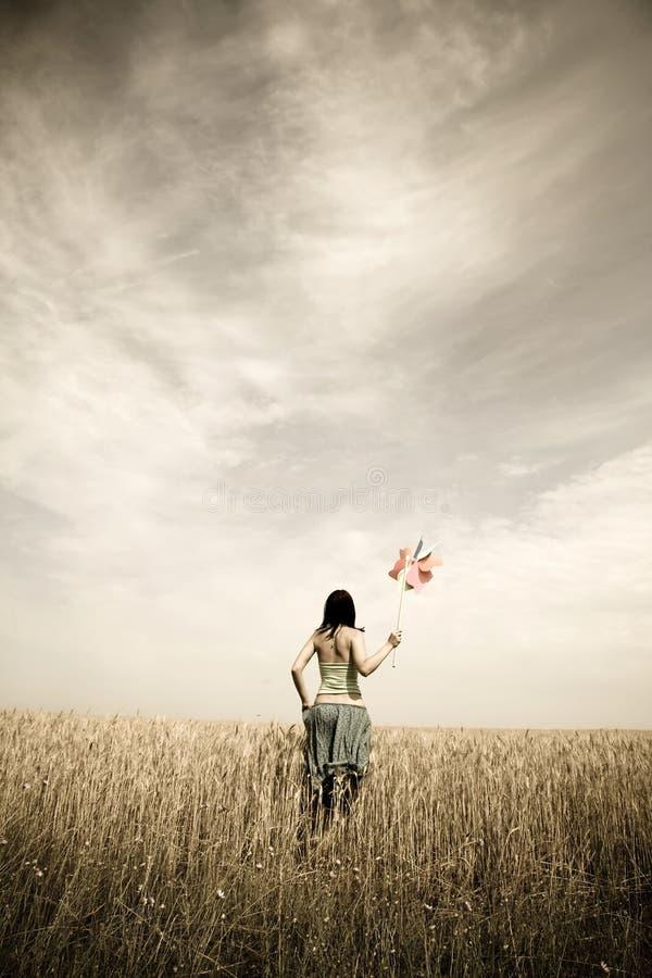 Muchacha con la turbina de viento del juguete en el campo fotos de archivo