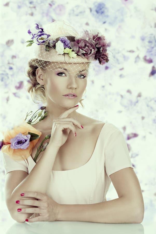 Muchacha con las flores en el sombrero y la mano debajo de la barbilla imagenes de archivo