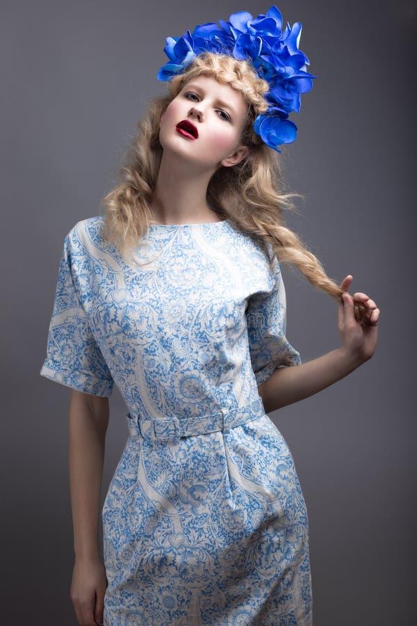 Muchacha con las flores en su cabeza en un vestido en el estilo ruso fotografía de archivo libre de regalías