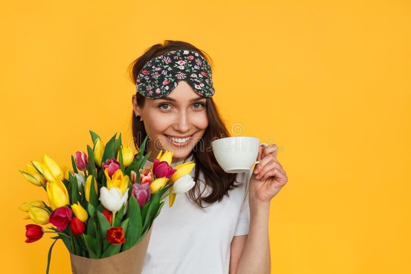 Muchacha con las flores y el café de la máscara el dormir imagenes de archivo