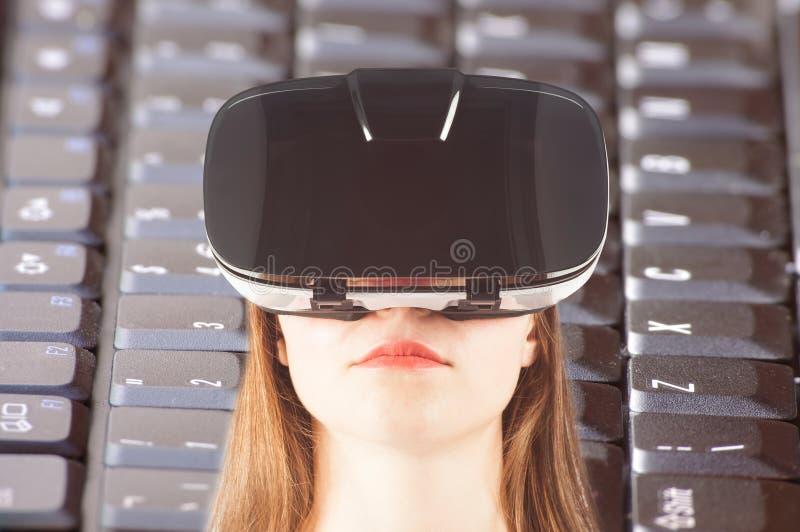 Muchacha con las gafas de la realidad virtual y el teclado de ordenador imagenes de archivo
