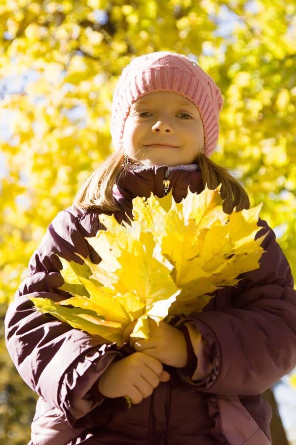 Muchacha con las hojas de otoño al aire libre fotos de archivo