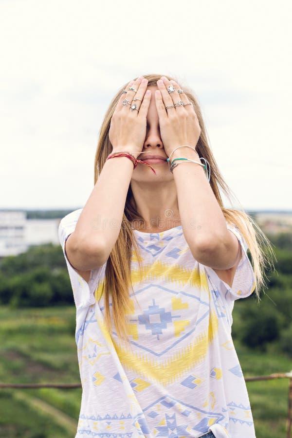 Muchacha con las manos cerradas de los ojos fotografía de archivo