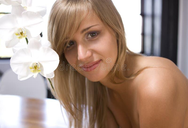 Muchacha con las orquídeas blancas imagenes de archivo