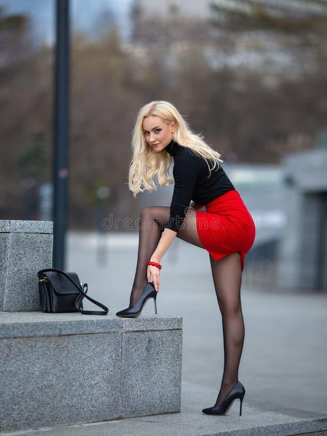 Muchacha con las piernas perfectas en panty en el cuadrado de ciudad foto de archivo libre de regalías