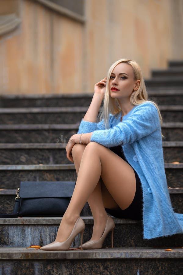Muchacha con las piernas perfectas que presentan en el parque del otoño imagenes de archivo