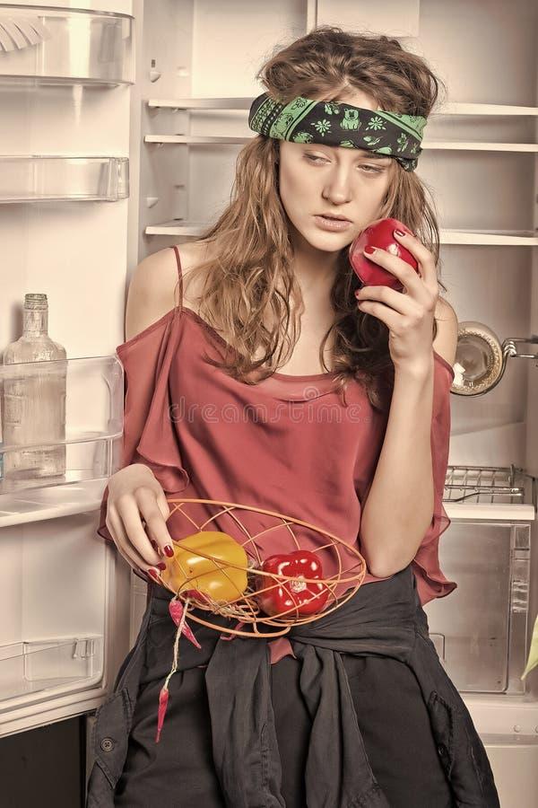 Muchacha con las pimientas dulces que se colocan en el refrigerador fotos de archivo libres de regalías