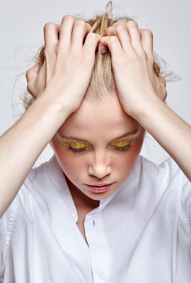 Muchacha con las sombras de ojos y las manos ahumadas amarillas de los ojos en la cabeza imagenes de archivo