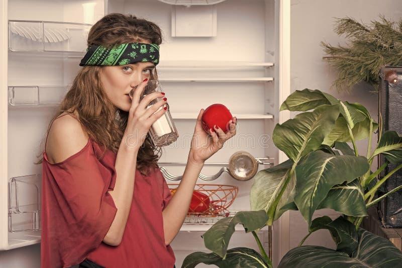 Muchacha con leche de consumo del pelo rizado Venda que lleva de la mujer que lleva a cabo la manzana, las vitaminas y concepto r imagenes de archivo