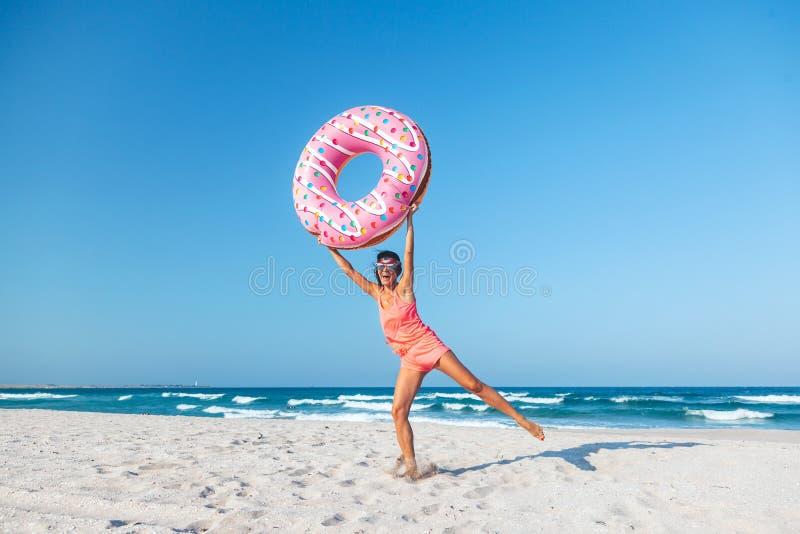 Muchacha con lilo del buñuelo en la playa imagenes de archivo