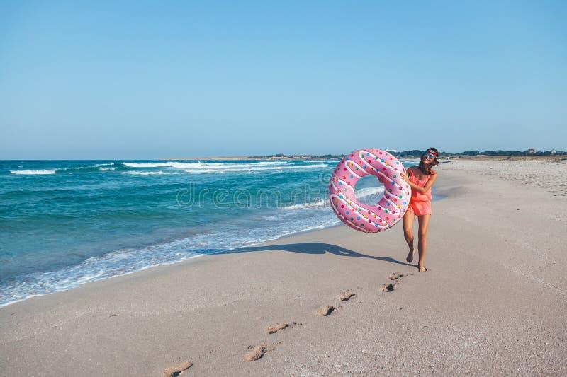 Muchacha con lilo del buñuelo en la playa foto de archivo libre de regalías