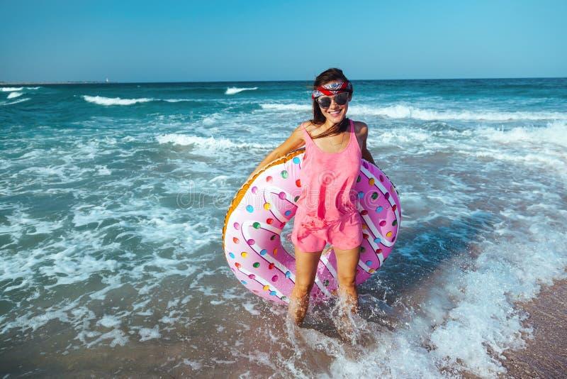 Muchacha con lilo del buñuelo en la playa imagen de archivo libre de regalías