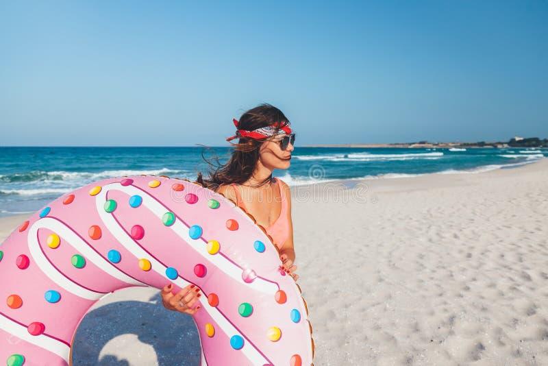 Muchacha con lilo del buñuelo en la playa fotos de archivo