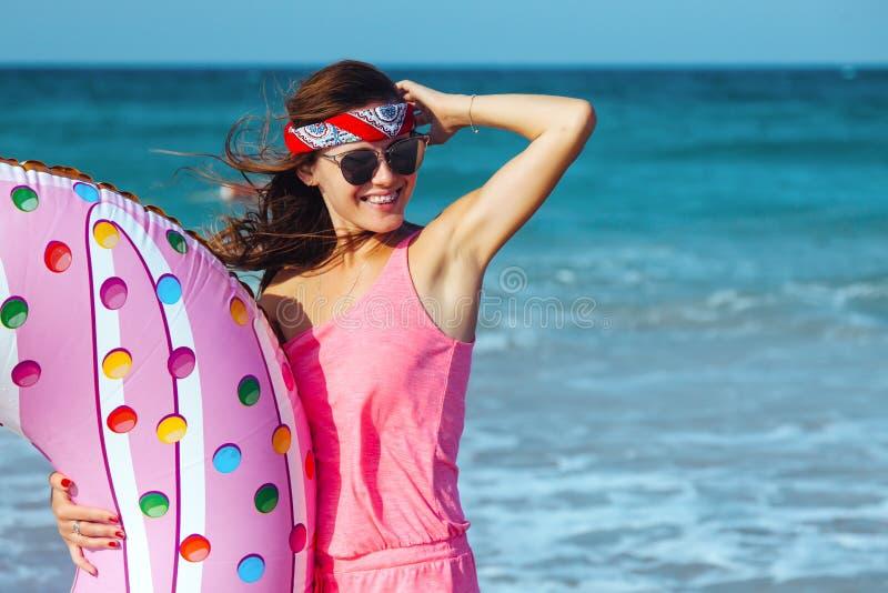 Muchacha con lilo del buñuelo en la playa imagen de archivo