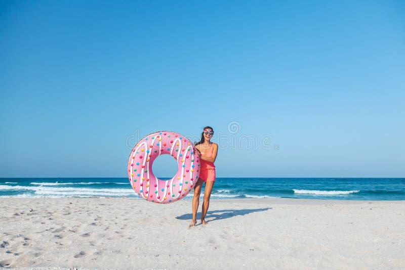 Muchacha con lilo del buñuelo en la playa fotografía de archivo