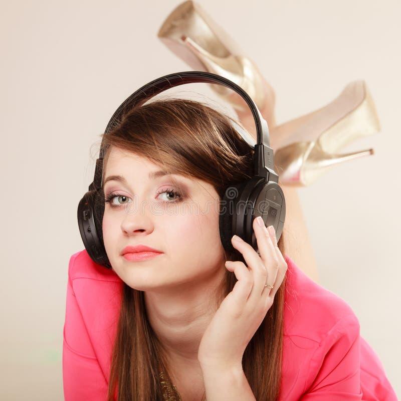 Muchacha con los auriculares negros que escucha la música imagen de archivo