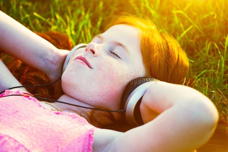 Muchacha con los auriculares que escucha la música foto de archivo libre de regalías