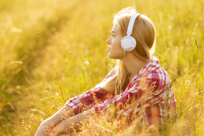 Muchacha con los auriculares que se sientan en la hierba foto de archivo libre de regalías