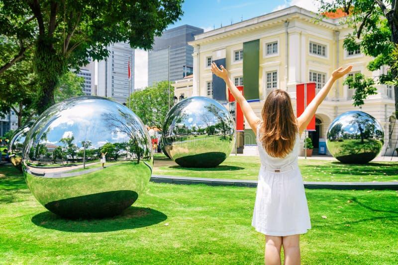 Muchacha con los brazos aumentados entre sorprender las bolas de espejo grandes fotografía de archivo