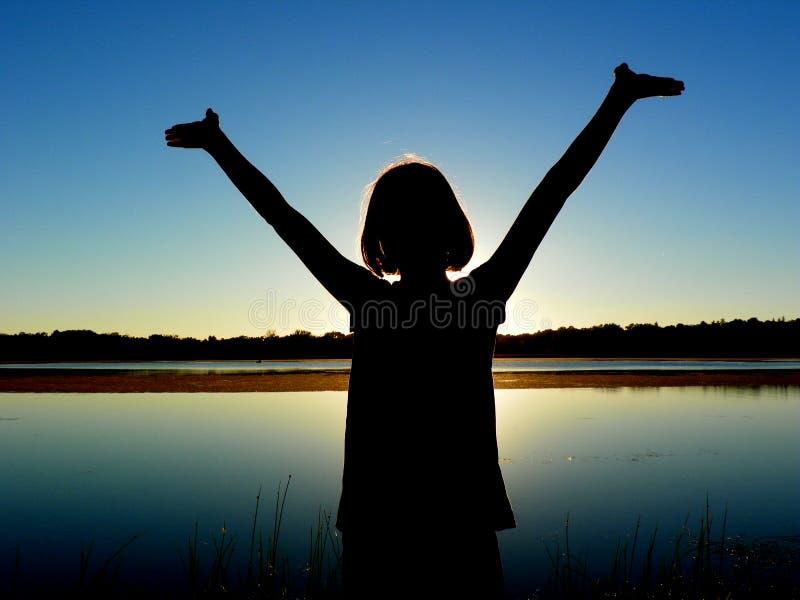 Muchacha con los brazos aumentados por el lago foto de archivo