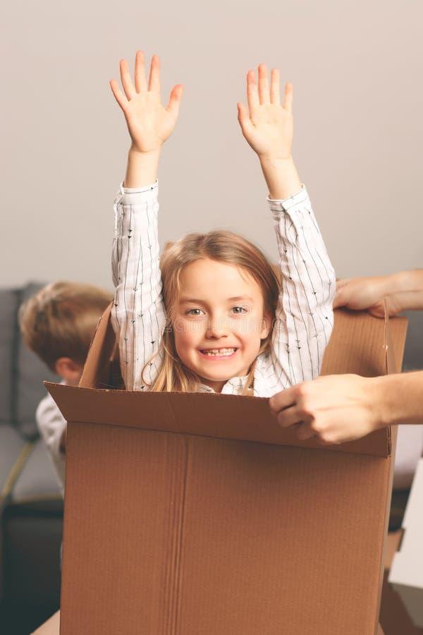 Muchacha con los brazos aumentados que se sientan en caja de cartón imagen de archivo