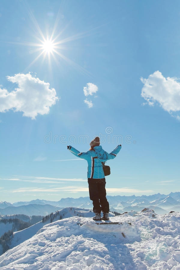 Muchacha con los brazos extendidos, colocándose en el top de la montaña, la del invierno foto de archivo libre de regalías