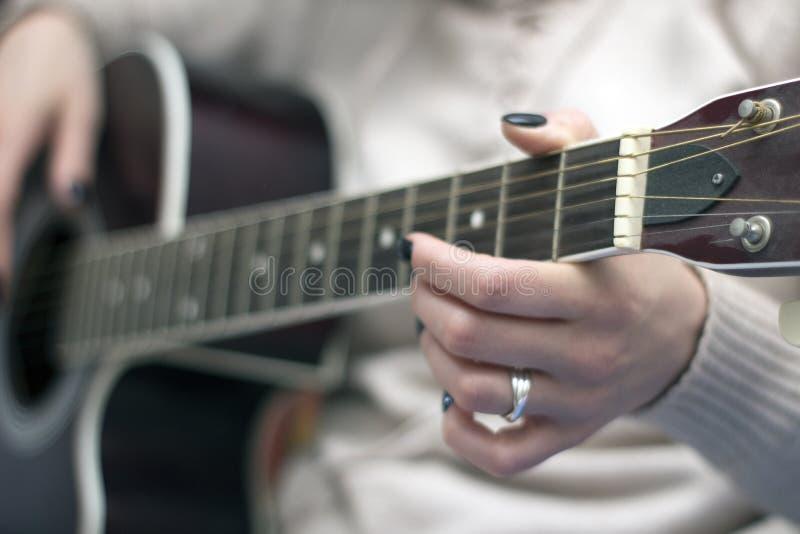 muchacha con los clavos negros que juegan secuencias de la guitarra foto de archivo libre de regalías