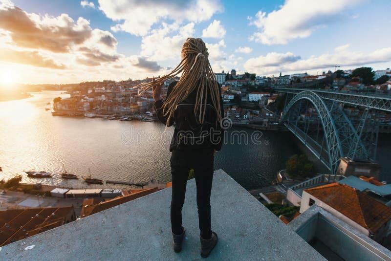 Muchacha con los dreadlocks rubios que colocan en el fondo del puente Dom Luis I sobre el río del Duero, Oporto imagen de archivo libre de regalías