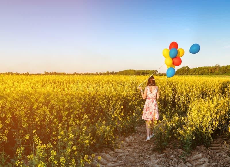 Muchacha con los globos en campo floreciente imagen de archivo