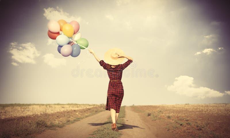 Muchacha con los globos y el bolso multicolores imagen de archivo