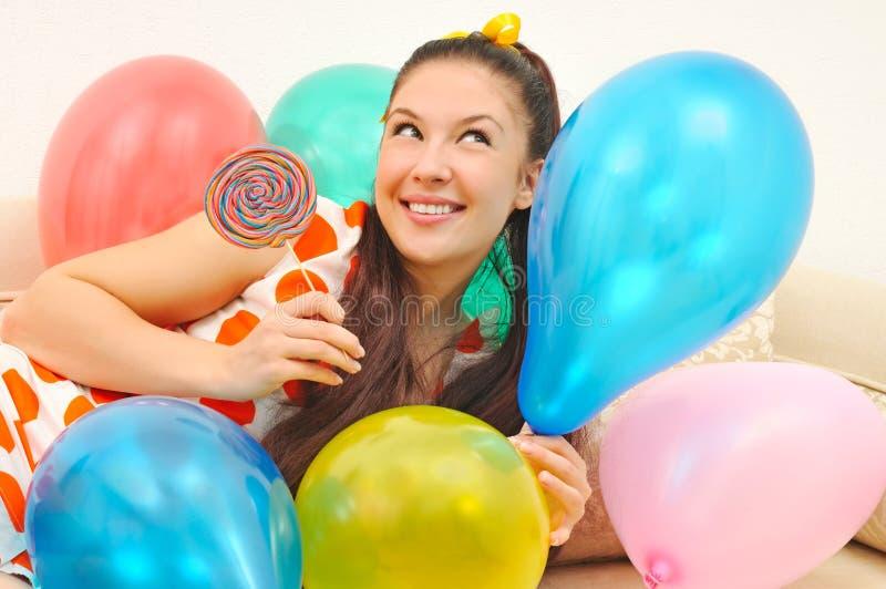 Muchacha con los globos y el caramelo imagen de archivo