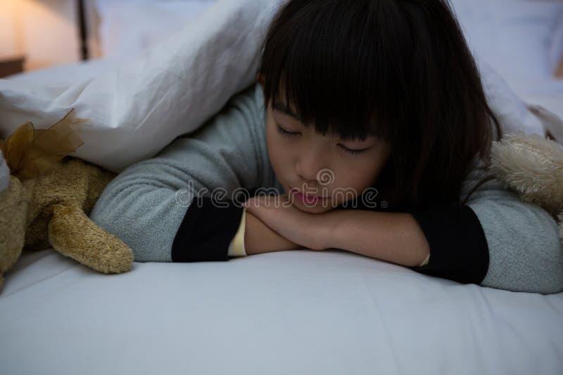 Muchacha con los juguetes que descansan sobre cama imagen de archivo libre de regalías
